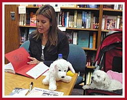 Jana Kolh signs a copy of A Rare Breed of Love as Baby the puppy mill survivor watches.